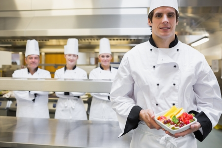 Chef holding fruit salad with team standing behind him in kitchen photo