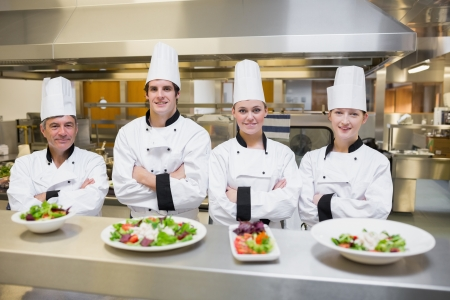 chefs whites: Smiling Chefs standing behind salads in the kithcen Stock Photo