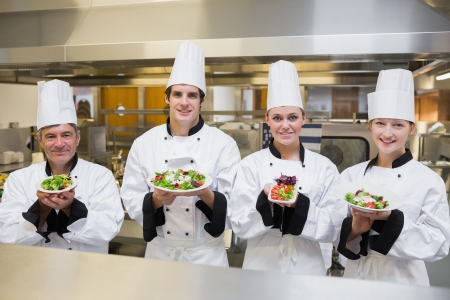 Chef's presenting different salads in the kitchen photo
