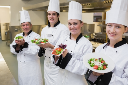 Happy Chef's presenting their salads in the kitchen photo