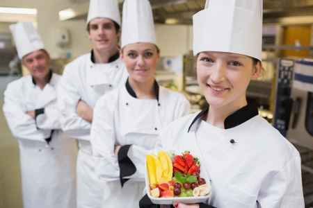 Chef presenting a fruit salad with team of Chef's in kitchen photo