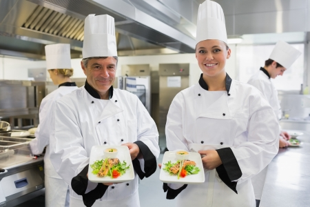 Two Chef's showing salmon dishes in the kitchen photo