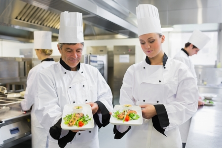 Two Chef's presenting their salmon dishes in the kitchen Stock Photo - 16065908