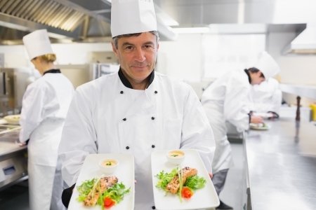 Chef holding out two salmon dishes in the kitchen photo
