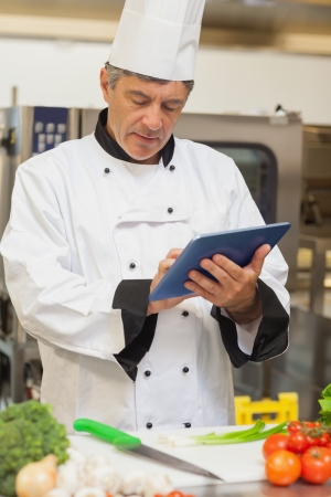 chef knife: Chef using digital tablet in the kitchen Stock Photo