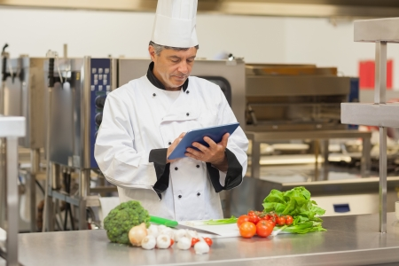 Chef preparing recipe with digital tablet in the kitchen photo
