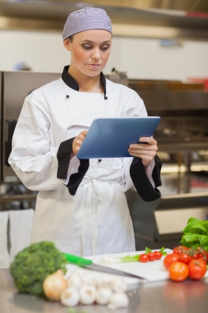 Chef consulting digital tablet beside vegetables in the kitchen photo
