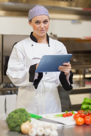 Chef using digital tablet and smiling in the kitchen photo