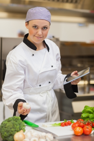 Chef smiling and holding digital tablet and mushroom in the kitchen photo