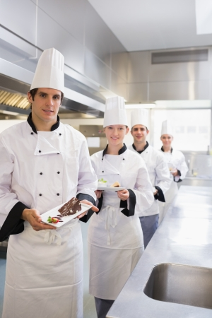Team of Chef's presenting deserts in the kitchen photo