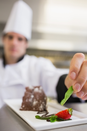 Mint leaf being put onto dessert plate of chocolate cake by chef photo