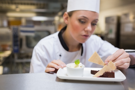 Chef garnishing a slice of cake in the kitchen photo