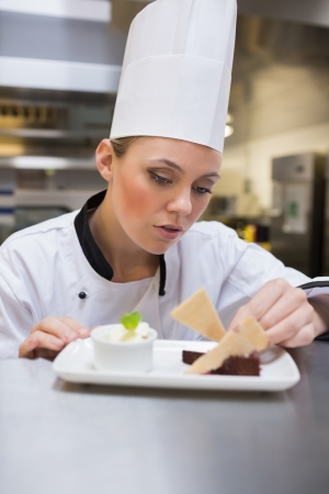 Chef carefully garnishing desert in the kitchen photo
