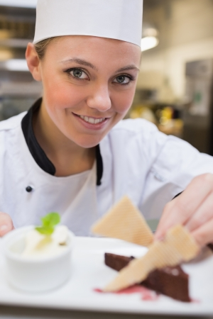 chefs whites: Smiling chef garnishing a slice of cake with wafers in the kitchen