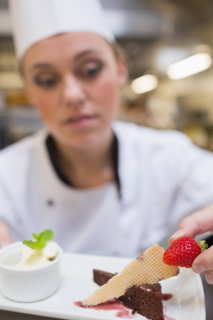 dessert stand: Chef putting strawberry on dessert plate in the kitchen Stock Photo