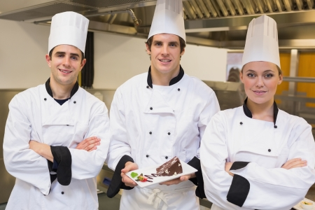 Three Chefs presenting a cake in the kitchen photo