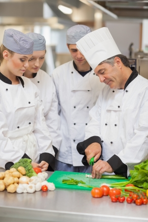 Chef teaching cutting vegetables to three trainees in the kitchen photo