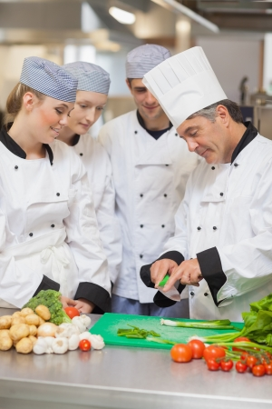 cookers: Chef teaching trainees how to cut vegetables in the kitchen