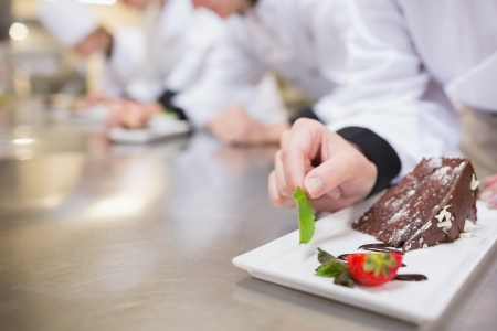 garnishing: Chocolate cake being garnished by chef in the kitchen