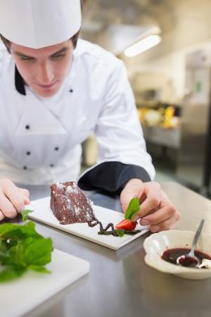 chef cocinando: Chef menta poner en el plato de postre con la torta en la cocina