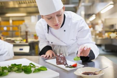 comida gourment: Chef poner menta con su pastel de chocolate en la cocina