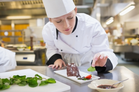 cooking chef: Chef putting mint with her chocolate cake in the kitchen