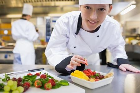 fruit salad: Happy chef preparing fruit salad in kitchen Stock Photo