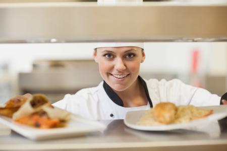 kitchen restaurant: Chef handing dinner plates through order station in the kitchen