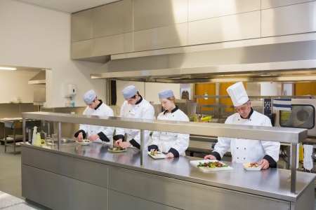Four Chef's preparing plates in the kitchen photo