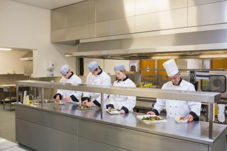 garnishing: Four Chefs preparing plates in the kitchen