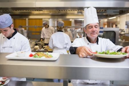 control de calidad: El jefe de cocina de cheques ensalada en la cocina antes del servicio Foto de archivo
