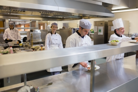 Restaurant kitchen with four Chefs cooking and working photo