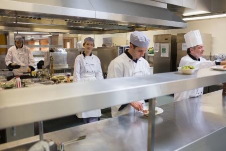 chef cocinando: Restaurante cocina con cuatro chef de cocina y de trabajo Foto de archivo