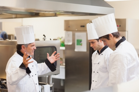 Head chef scolding employees in the kitchen photo