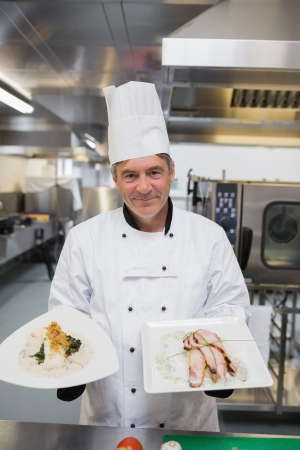 Chef presenting two chicken dishes in kitchen photo