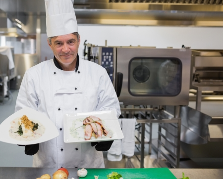 Smiling chef holding two chicken plates in the kitchen photo