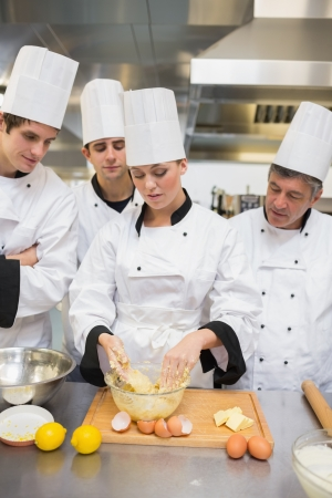 Trainees learning how to prepare dough in the kitchen