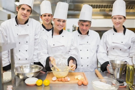 Smiling culinary class with pastry teacher in kitchen Stock Photo