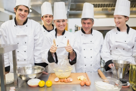 chefs whites: Culinary class with pastry teacher giving thumbs up in kitchen