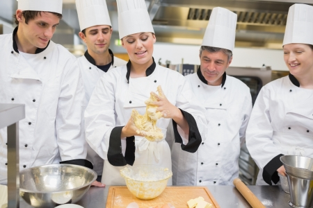 Class watching pastry teacher forming the dough in kitchen photo