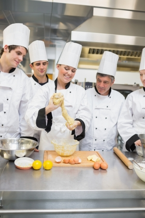pastry chef: Smiling pastry teacher showing class how to form dough in the kitchen Stock Photo