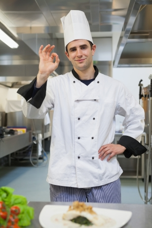 Smiling chef giving ok symbol in the kitchen photo