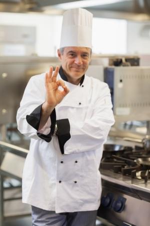 ok symbol: Chef dando simbolo ok dalla stufa in cucina