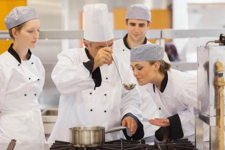 mujeres cocinando: Estudiante degustar la sopa del profesor en la escuela de cocina