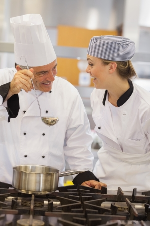 chefs whites: Smiling student and teacher discussing the soup in the kitchen
