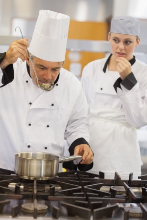 Teacher tasting his students soup with her watching anxiously in kitchen of culinary school photo