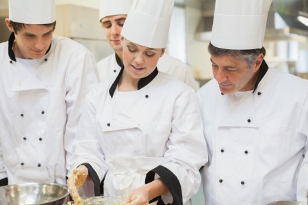 Trainee Chefs learning how to mix dough in kitchen photo