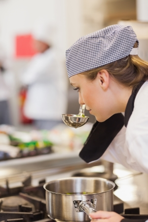 female chef: Chef smelling her soup on the stove in the kitchen