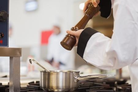 Chef Hinzufügen Pfeffer-Suppe im Topf auf dem Herd in der Küche Standard-Bild