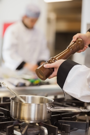 Pepper being added to soup in pot by chef